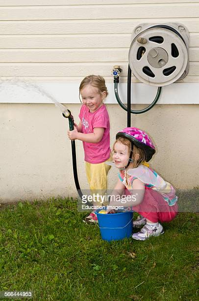 Leavenworth Kansas 3 year old girls playing with garden hose