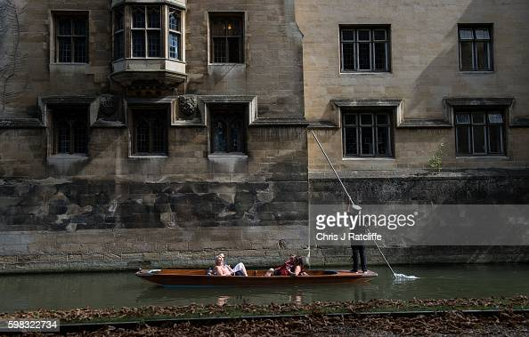 Leaves fall and lie on a footpath as a punter in a captain's hat takes tourists past King's College on the River Cam on September 1 2016 in Cambridge...