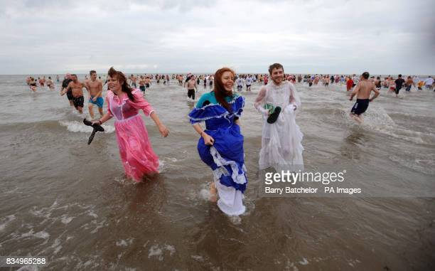 Leaving the sea after participating in the Porthcawl Christmas Morning Swim in South Wales are from left Lucy Ford Catherine Ford and Lucas Durant