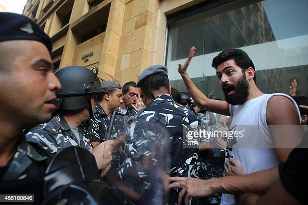 A Lebanese activist gestures towards a policeman outside the environment ministry in downtown Beirut on September 1 2015 as Lebanese police started...