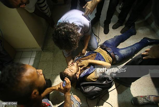 A Lebanese activist is assisted after falling unconscious in the environment ministry in downtown Beirut on September 1 2015 as Lebanese police...