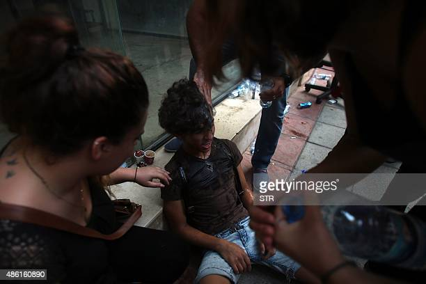 A Lebanese activist is assisted after falling unconscious outside the environment ministry in downtown Beirut on September 1 2015 as Lebanese police...