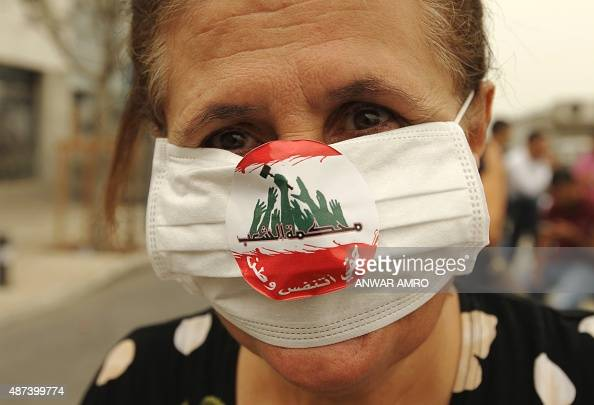 A Lebanese activist wears a mask during a protest denouncing Lebanon's stagnant political system that has become the target of demonstrations...