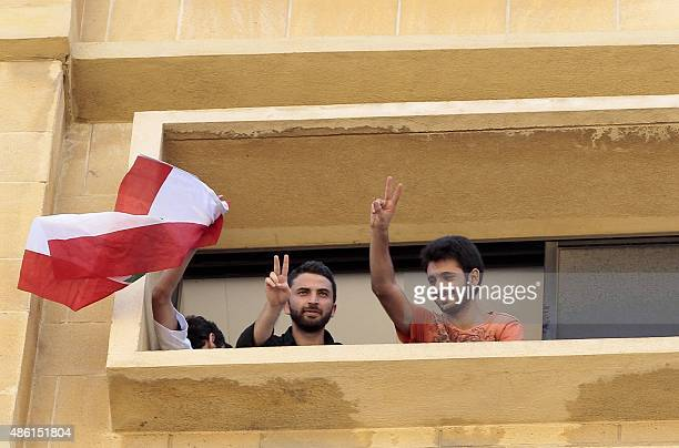 Lebanese activists flash the sign of victory from a window during a surprise sitin at Lebanon's environment ministry to demand the minister's...