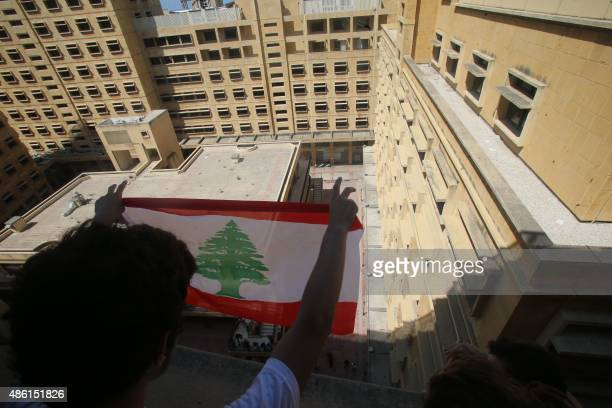 Lebanese activists hold a national flag from a window during a surprise sitin at Lebanon's environment ministry to demand the minister's resignation...