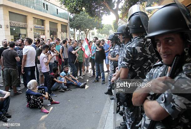 Lebanese activists stand in front of riot police outside the environment ministry in downtown Beirut on September 1 2015 as Lebanese police started...