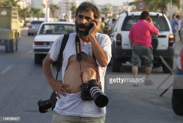 Lebanese AFP photographer Mahmoud Zayyat speaks on his mobile phone after being manhandled by Lebanese security forces as he covered a sitin in the...