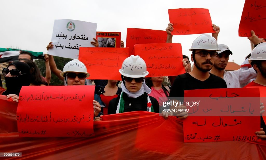 Lebanese and Syrian protesters hold banners as they take part in a demonstration in front of United Nations offices in Beirut in solidarity with the civilians of the northern Syrian city of Aleppo and against the regime of the Syrian president, on May 1, 2016. / AFP / Anwar AMRO