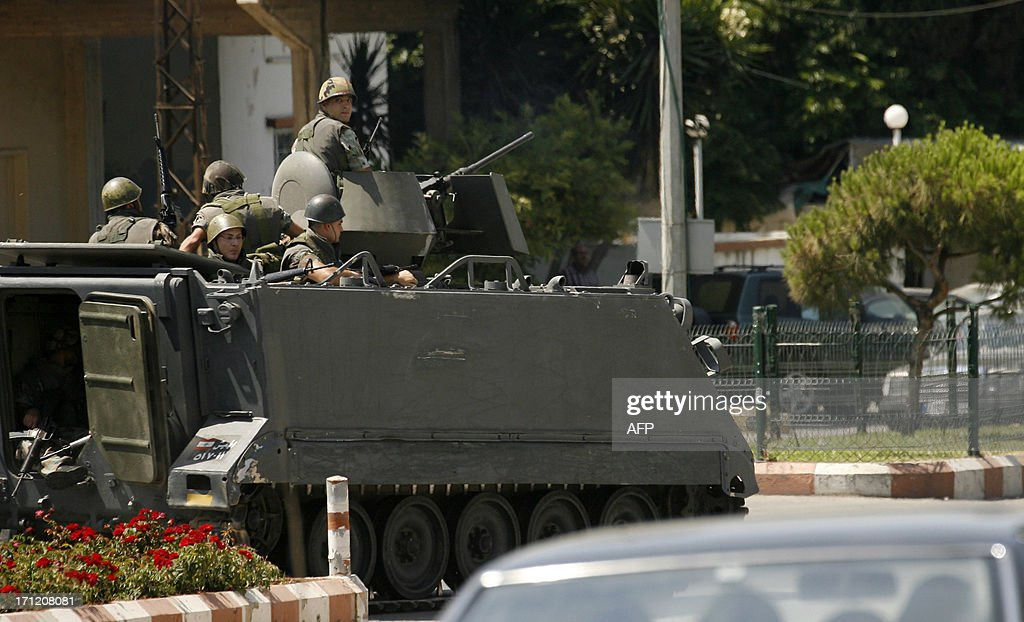 Lebanese army forces monitor a street in the village of Abra, on the outskirts of the southern Lebanese city of Sidon, during clashes between Lebanese army personnel and supporters of radical Sunni Muslim sheikh, Ahmad al-Assir, who oppose the powerful Shiite movement Hezbollah on June 23, 2013. The fighting erupted when Assir supporters surrounded an army checkpoint in Abra, where a vehicle transporting other supporters of the Sunni cleric had been stopped, a security source told AFP. AFP PHOTO / MAHMOUD ZAYYAT