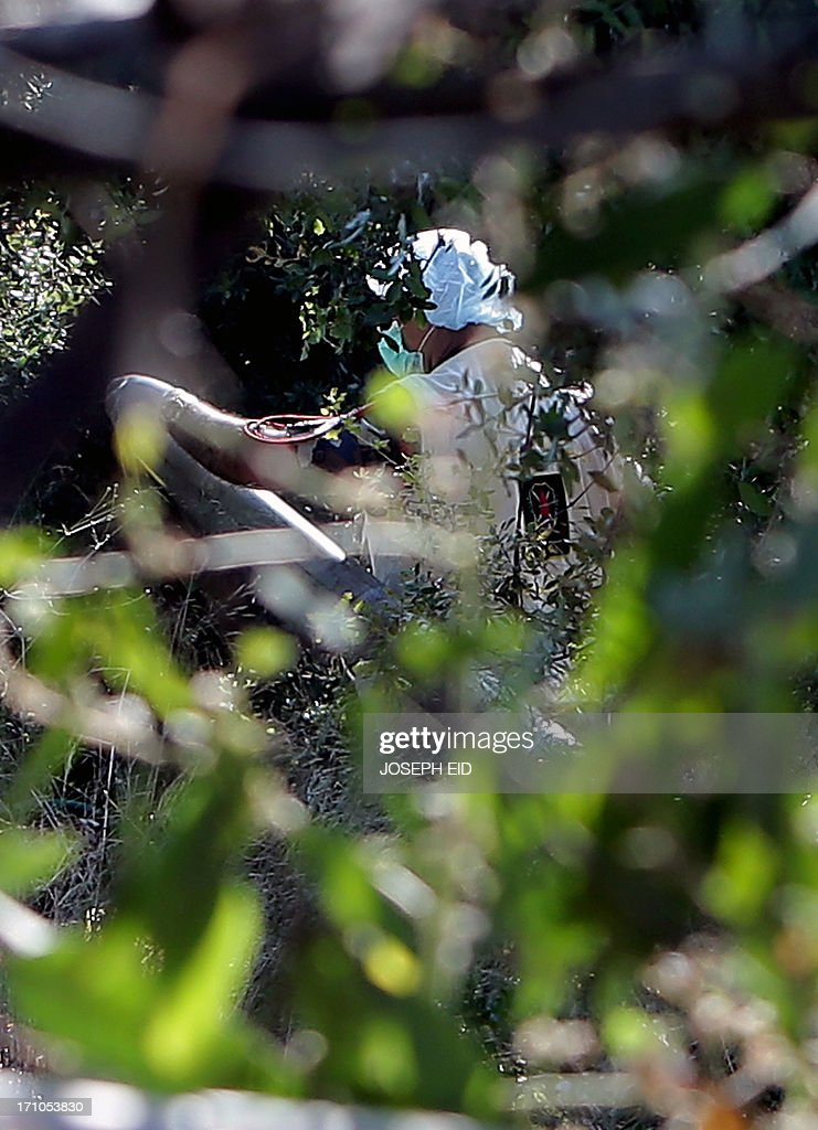 A Lebanese Army forensic investigator inspects a missile which failed to launch hidden between shrubbery in the Balluneh area, north of Beirut, on June 21, 2013. A Grad rocket fired from north of the Lebanese capital exploded near the city overnight, a security source said, adding that the army also found a second rocket at the launch site. AFP PHOTO/JOSEPH EID
