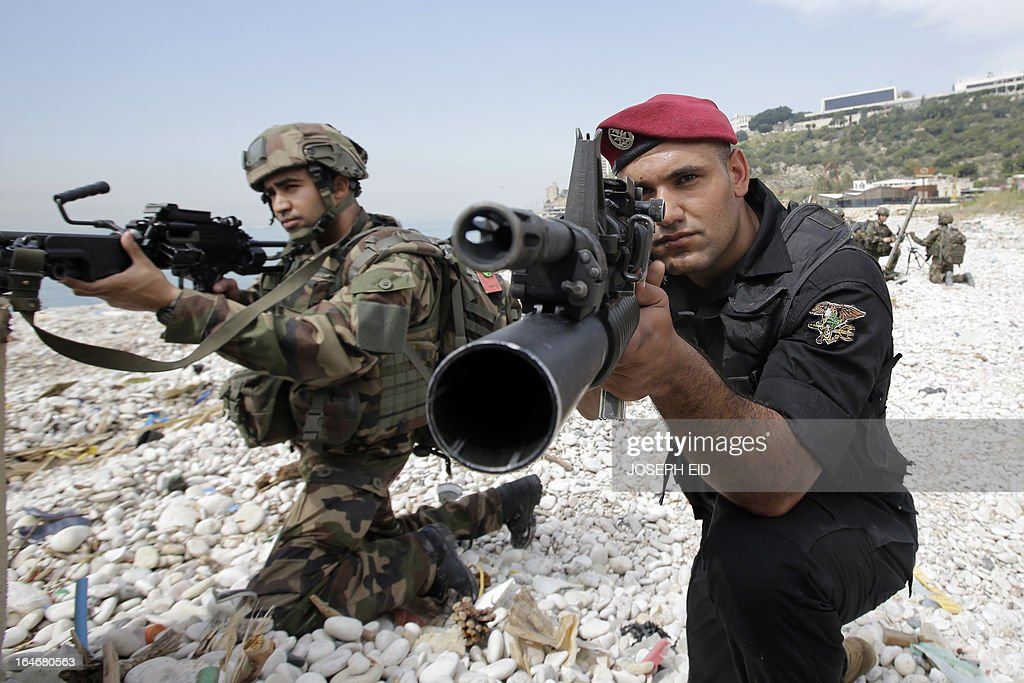 A Lebanese Army Navy Seal (R) takes position next to a Lebanese soldier as they take part in sea and land war games with the French Army at the bay of Jounieh, north of Beirut, on March 26, 2013. AFP PHOTO/JOSEPH EID