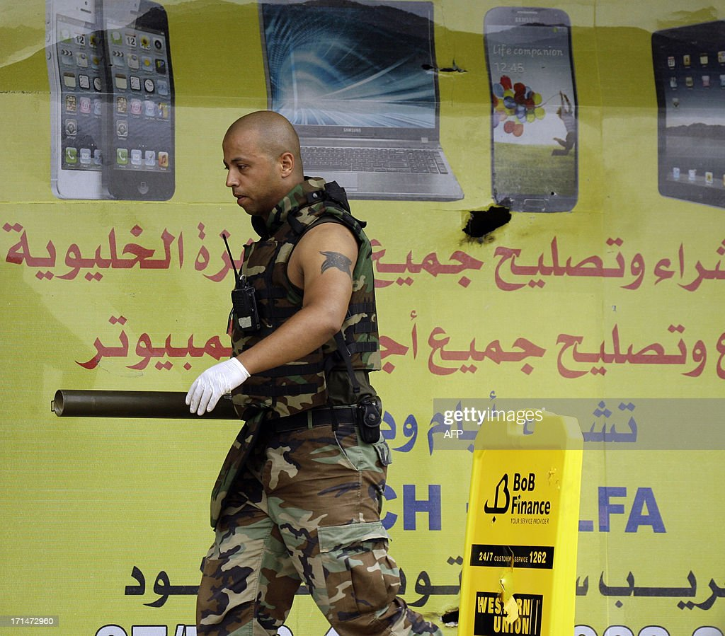 A Lebanese Army soldier carries a weapon secured from the Bilal bin Rabah mosque in the Abra district of the southern city of Sidon on June 25, 2013, after troops seized control of the headquarters of a radical Sunni sheikh whose supporters battled the army for two days, killing 16 soldiers.