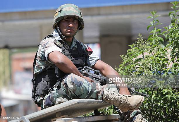 A Lebanese army soldier sits atop an armoured personnel carrier as government troops were deployed on the road leading the northeastern Lebanese town...