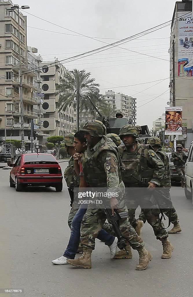Lebanese army soldiers arrest a suspect as they patrol a street in the northern coastal city of Tripoli during clashes between pro- and anti-Syrian regime local gunmen on March 22, 2013. Tripoli has been rocked by deadly clashes between supporters and opponents of Syrian President Bashar al-Assad, where a two-year conflict has killed at least 70,000 people according to UN estimates. AFP PHOTO/JOSEPH EID