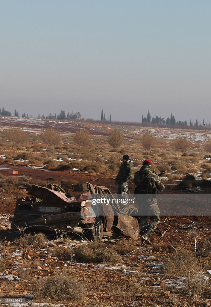 Lebanese army soldiers stand next to the wreckage of a car following an explosion in the village of Sbouba east of Baalbek in Lebanon's Bekaa valley, on December 17, 2013. A car exploded near a Hezbollah checkpoint in eastern Lebanon early in the morning, causing both deaths and injuries, a security source told AFP on condition of anonymity. AFP PHOTO/STR