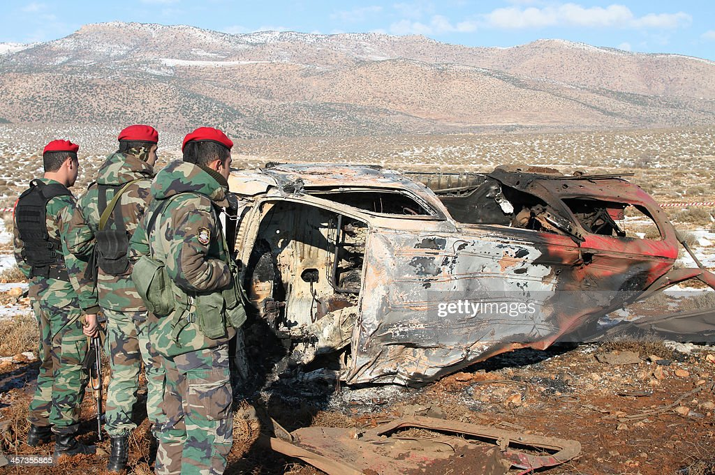 Lebanese army soldiers stand next to the wreckage of a van following an explosion in the village of Sbouba east of Baalbek in Lebanon's Bekaa valley, on December 17, 2013. A car exploded near a Hezbollah checkpoint in eastern Lebanon early in the morning, causing both deaths and injuries, a security source told AFP on condition of anonymity.