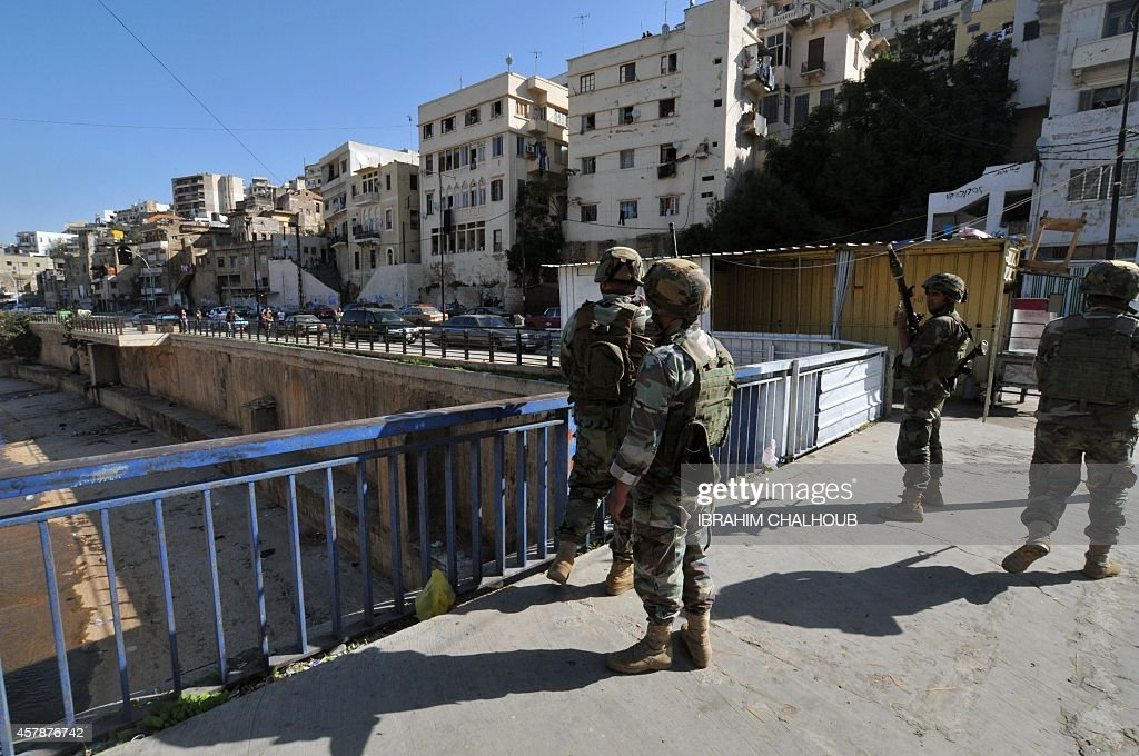 Lebanese army soldiers stand on a bridge over the Abu Ali river where the bodies of two young Sunni men were found on October 26 2014 next to the...