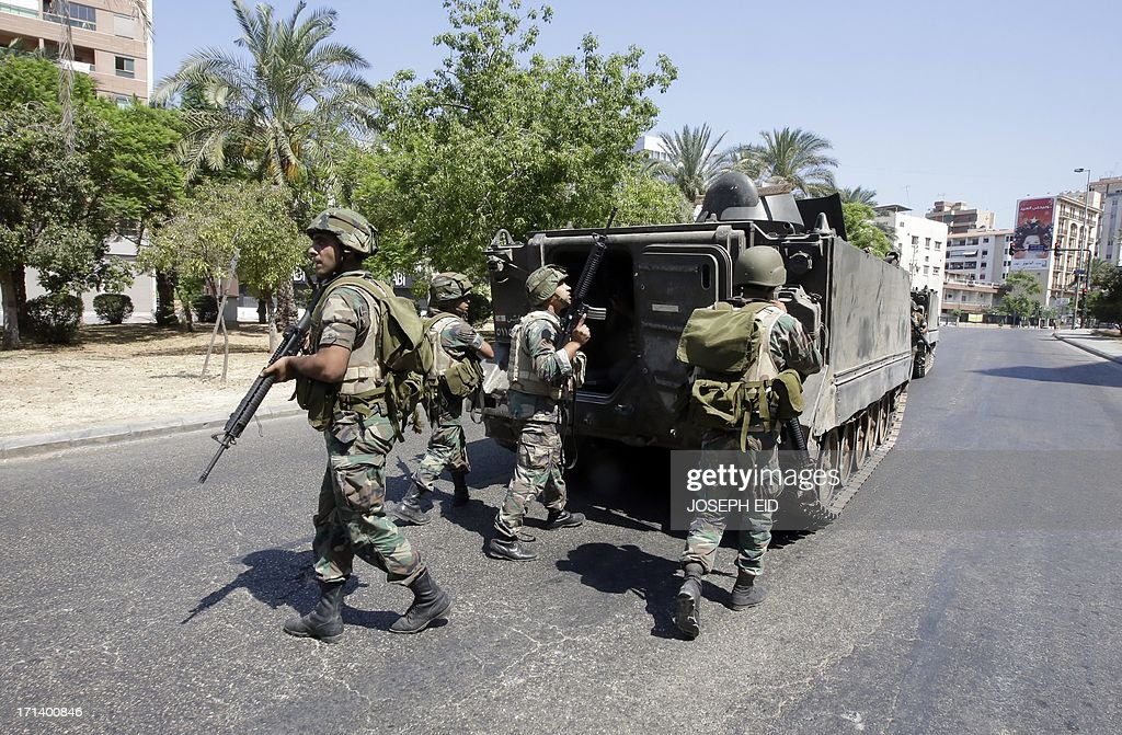 Lebanese Army soldiers take cover behind their armoured vehicle as they enter the Abra neighbourhood on the eastern outskirts of Sidon, where fighting is now concentrated between the army and supporters of a Sunni Muslim radical cleric, on June 24, 2013. At least 12 Lebanese soldiers have been killed in less than 24 hours of clashes with supporters of the radical Sunni cleric Sheikh Ahmad al-Assir in the southern city of Sidon, a military spokesman told
