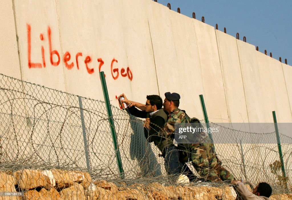 A Lebanese army's soldier prevents a protestor from writing in French 'Free Georges Abdallah' during a demonstration to call for his release outside the United Nations Interim Force in Lebanon (UNIFIL) French base on January 19, 2013 in the southern city of Deir Kifa. George Ibrahim Abdallah was sentenced to life imprisonment in France in 1984 for his part in the 1982 murders of two diplomats, Charles Robert Day, an American and Yacov Barsimantov, an Israeli, in Paris.