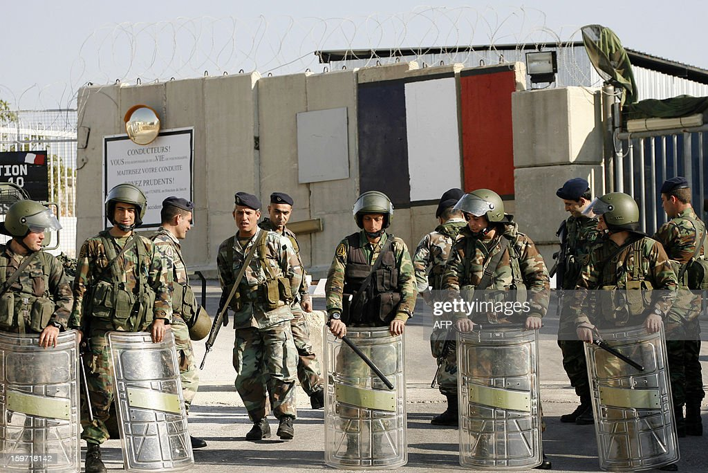 Lebanese army's soldiers stand guard at the entrance of the the United Nations Interim Force in Lebanon (UNIFIL) French base during a demonstration of protestors calling for the release of Georges Abdallah on January 19, 2013 in the Lebanese southern city of Deir Kifa. George Ibrahim Abdallah was sentenced to life imprisonment in France in 1984 for his part in the 1982 murders of two diplomats, Charles Robert Day, an American and Yacov Barsimantov, an Israeli, in Paris. AFP PHOTO MAHMOUD ZAYYAT
