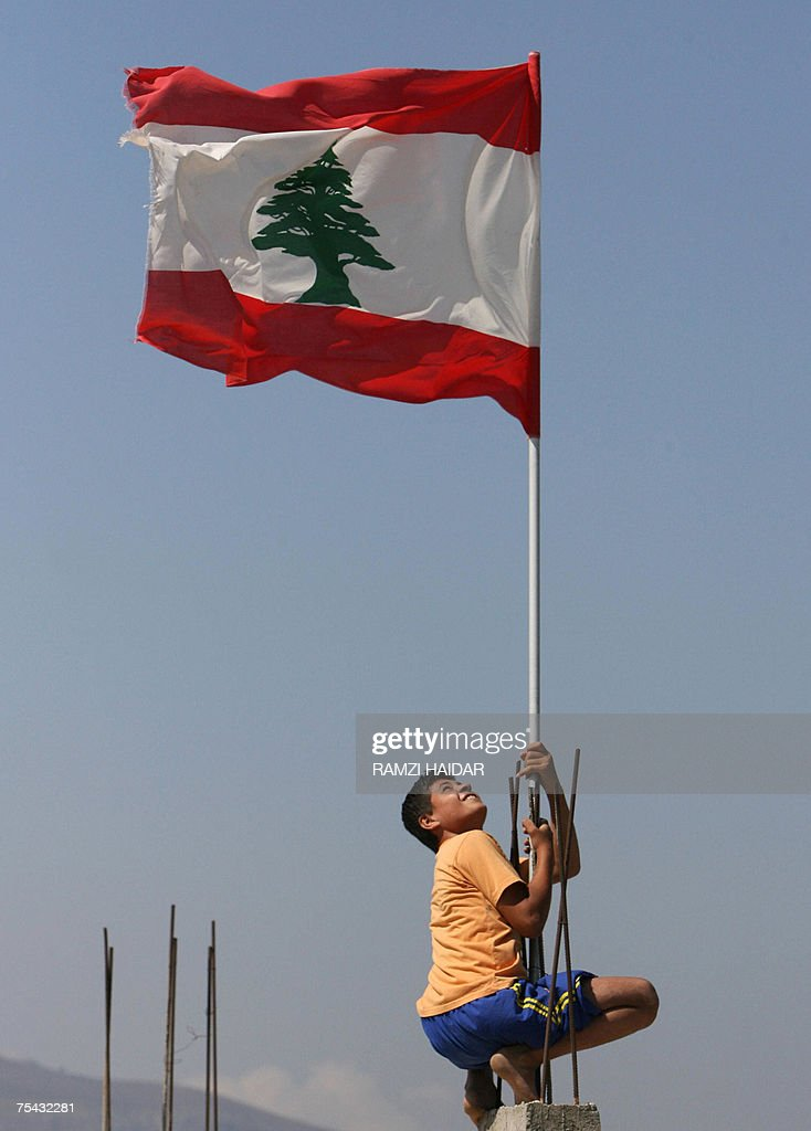 Lebanese boy hangs onto a Lebanese flag poll at the entrance of the Palestinian refugee camp of Nahr al-Bared, 16 July 2007. Two Lebanese soldiers were killed today as the army continued to make advances in its eight-week-old battle to crush Islamists besieged in the refugee camp.