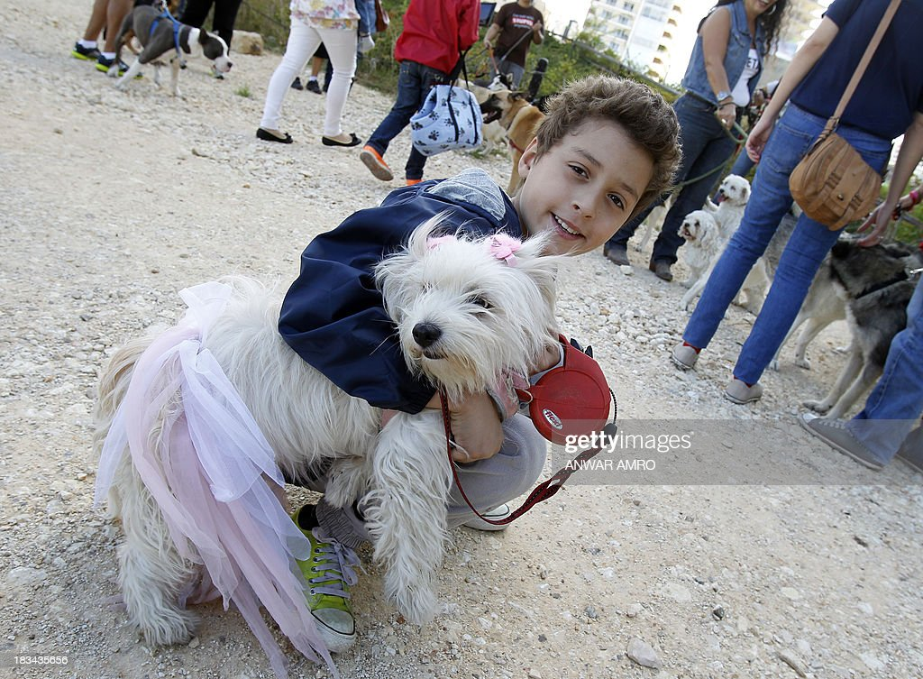 A Lebanese boy poses with his dog in Martyr's Square in downtown Beirut at the start of march along the Corniche organised by Beirut for the Ethical Treatment of Animals (BETA) on October 6, 2013 in support of the improvement of animal welfare in the region and to stop the abuse against them.