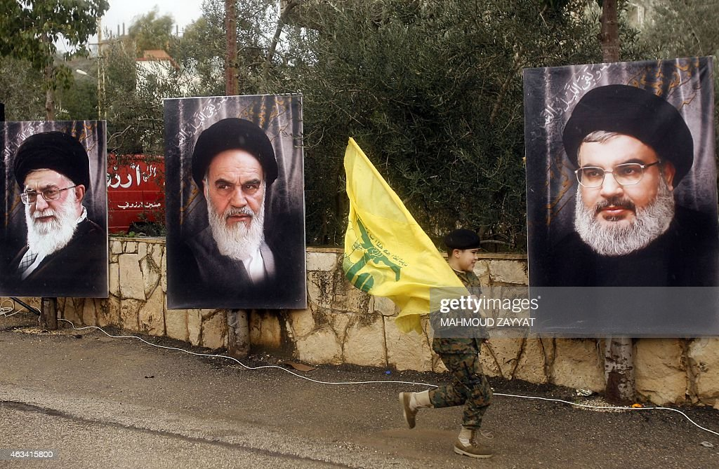 A Lebanese boy runs holding a Hezbollah flag past the portraits of Iran's Supreme Leader Ayatollah Ali Khamenei (L), founder of Iran's Islamic Republic, late Ayatollah Ruhollah Khomeini and Hezbollah leader Hassan Nasrallah on February 14, 2015 in the southern Lebanese town of Jibsheet. The Lebanese Shiite movement Hezbollah is marking today the death of three of its commanders, Abbas al-Mussawi, Ragheb Harb and Imad Mughnieh. Mussawi was killed on February 16, 1992 in an Israeli air raid on Nabatiyeh, Harb was assassinated in south Lebanon during Israel's occupation in February 1984 and Mughnieh was killed in a car bombing in the Syrian capital Damascus on February 12, 2008.