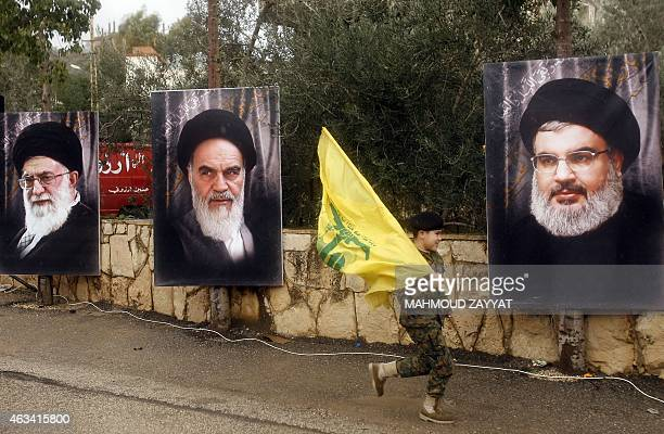 A Lebanese boy runs holding a Hezbollah flag past the portraits of Iran's Supreme Leader Ayatollah Ali Khamenei founder of Iran's Islamic Republic...
