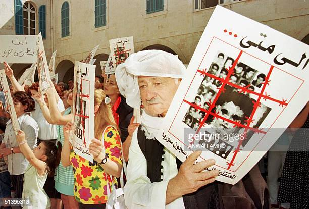 Lebanese Butros Doumyat the father of Adel who is held in a Syrian prison hold a poster of Lebanese prisoners during a sitin 24 September 2000 in...