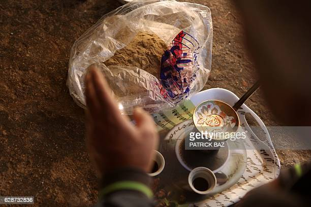 A Lebanese cannabis farmer talks to his Syrian employee over coffee and a bag full of cannabis powder in the village of Yammouneh located in the...