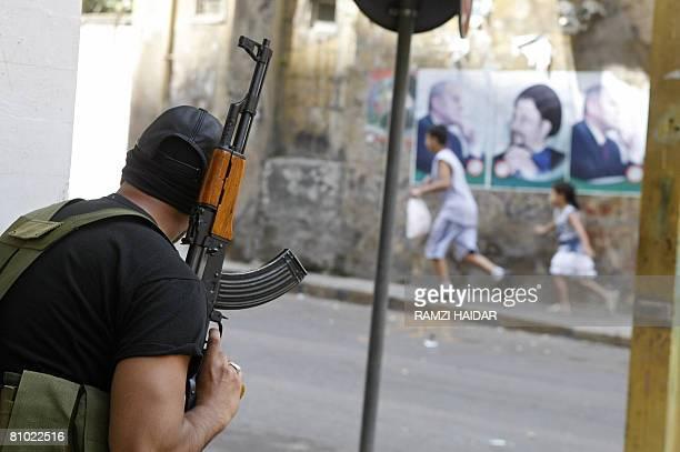 Lebanese children run past a gunman from Parliament Speaker Nabih Berri's Amal movement as he takes position in Beirut's Corniche alMazraa district...