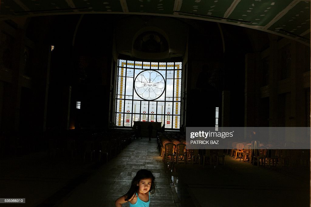 A Lebanese Christian girl plays in the Basilica of Our Lady of Mantara in the southern Lebanese town of Maghdouche East of Sidon on May 29, 2016 prior to a ceremony by the Ministry of Tourism to put the Grotto of Maghdouche on the international religious tourism map. Magdouche, along with Lourdes in France, Fatima in Portugal and Medugorje in Bosnia & Herzegovina are expected to be put on the international religious tourism map. According to local tradition the Virgin Mary accompanied Jesus during his journey to Tyre and to Sidon and waited for him in the grotto at Magdoucheh. The grotto was discovered 400 years ago. / AFP / Patrick BAZ