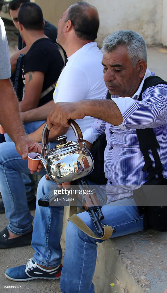 A Lebanese Christian man pours coffee into a cup while carrying a weapon on his lap as residents of the Christian village of al-Qaa, near the Lebanon's border with war-ravaged Syria, secure the area on June 28, 2016 after two waves of suicide bombings struck the village killing and wounding several people. At least five people were killed and 15 wounded in the pre-dawn attacks in the eastern village of Al-Qaa, in a hilly border area shaken by violence since Syria's conflict erupted in 2011. A security source said two of the attacks were near the municipality building in the centre of the village. / AFP / STRINGER