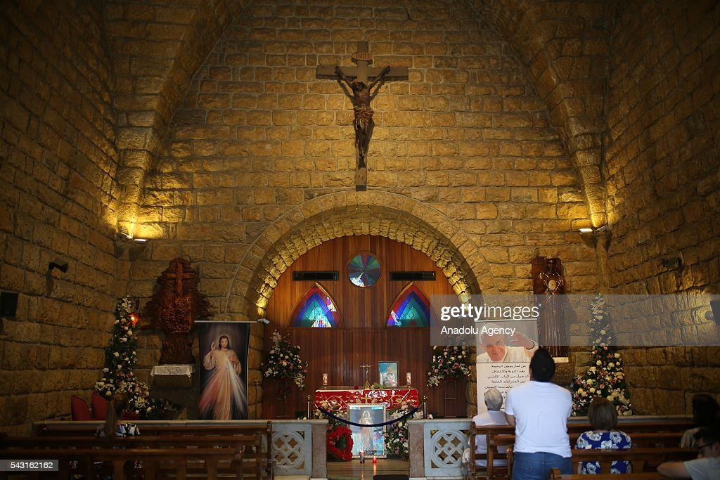 Lebanese Christian Maronites pray during a mass at the Shrine of Our Lady of Lebanon in the village of Harissa, 20 km north of Beirut on June 26, 2016.