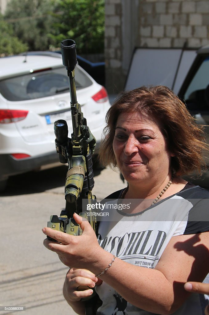 A Lebanese Christian woman holds a weapon as residents of the Christian village of al-Qaa, near the Lebanon's border with war-ravaged Syria, secure the area on June 28, 2016 after two waves of suicide bombings struck the village killing and wounding several people. At least five people were killed and 15 wounded in the pre-dawn attacks in the eastern village of Al-Qaa, in a hilly border area shaken by violence since Syria's conflict erupted in 2011. A security source said two of the attacks were near the municipality building in the centre of the village. / AFP / STRINGER