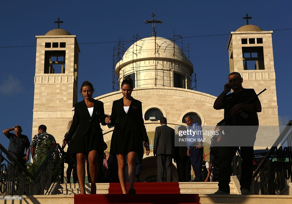 Lebanese Christian women walk the red carpet at a ceremony at the Basilica of Our Lady of Mantara in the southern Lebanese town of Maghdouche East of Sidon, on May 29, 2016, during the launch of an event by the Ministry of Tourism to put the Grotto of Maghdouche on the international religious tourism map. Magdouche, along with Lourdes in France, Fatima in Portugal and Medugorje in Bosnia & Herzegovina are expected to be put on the international religious tourism map. According to local tradition the Virgin Mary accompanied Jesus during his journey to Tyre and to Sidon and waited for him in the grotto at Magdoucheh. The grotto was discovered 400 years ago. / AFP / Patrick BAZ