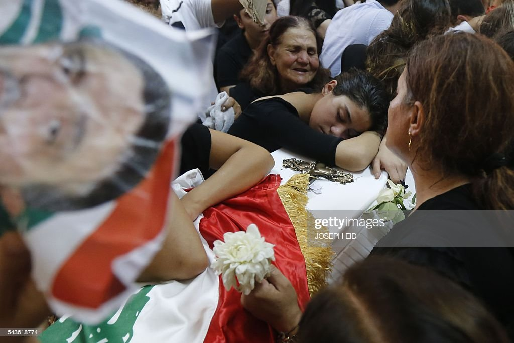 Lebanese Christians mourn over the coffin of a relative who was killed in a suicide attack earlier this week, on June 29, 2016, during a funeral in the village of al-Qaa, near the country's border with war-ravaged Syria. Two waves of suicide bombings struck the predominantly Christian village on June 27, killing and wounding several people before dawn and in the evening. / AFP / JOSEPH EID