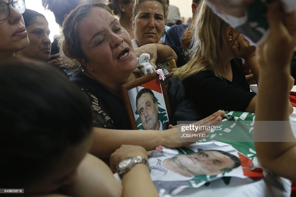 Lebanese Christians mourn over the coffin of a relative, who was killed in a suicide attack earlier this week, during his funeral in the village of al-Qaa, near the country's border with war-ravaged Syria, on June 29, 2016. Two waves of suicide bombings struck the predominantly Christian village on June 27, killing and wounding several people before dawn and in the evening. / AFP / JOSEPH EID