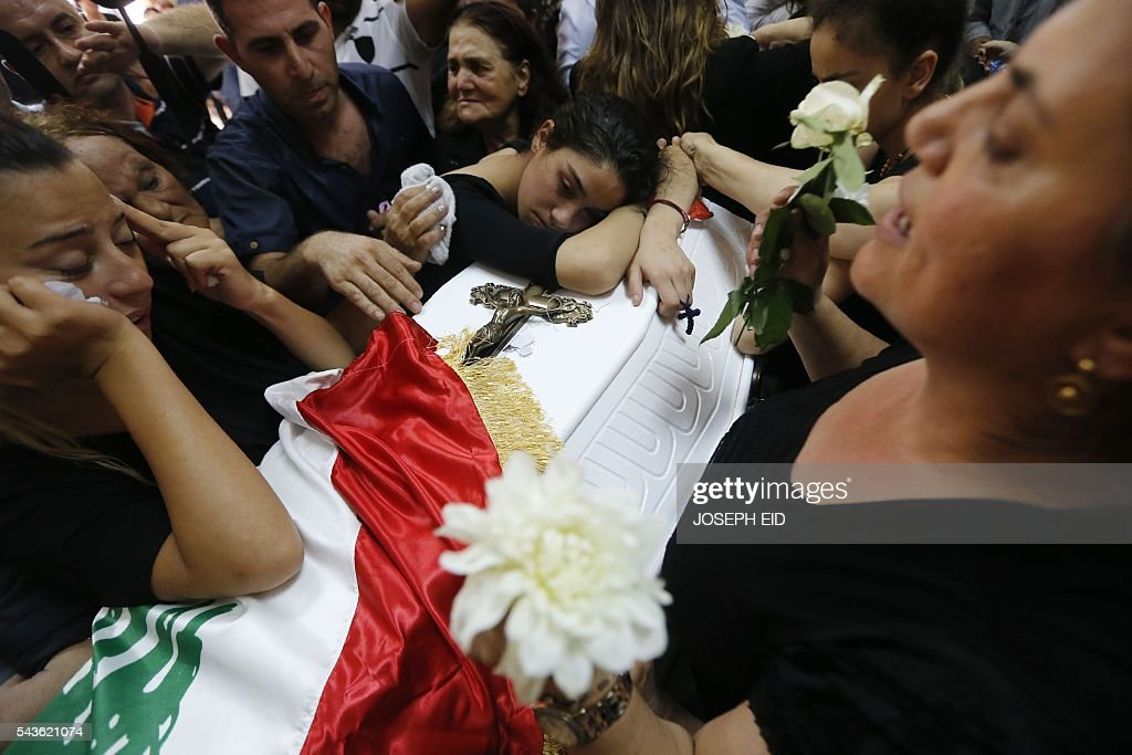 Lebanese Christians mourn over the coffin of a relative, who was killed in a suicide attack earlier this week, during a funeral ceremony in the village of al-Qaa, near the country's border with war-ravaged Syria, on June 29, 2016. Two waves of suicide bombings struck the predominantly Christian village on June 27, killing and wounding several people before dawn and in the evening. / AFP / JOSEPH EID