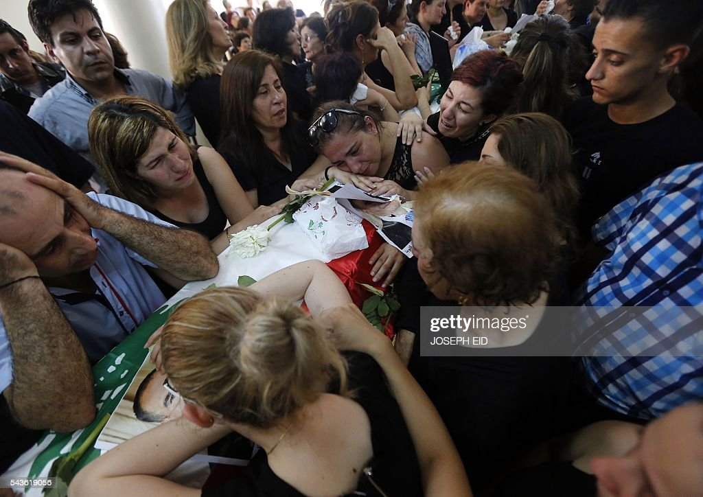 Lebanese Christians mourn over the coffins of relatives who were killed in suicide attacks earlier this week, on June 29, 2016, during their funeral in the village of al-Qaa, near the country's border with war-ravaged Syria. Two waves of suicide bombings struck the predominantly Christian village on June 27, killing and wounding several people before dawn and in the evening. / AFP / JOSEPH EID