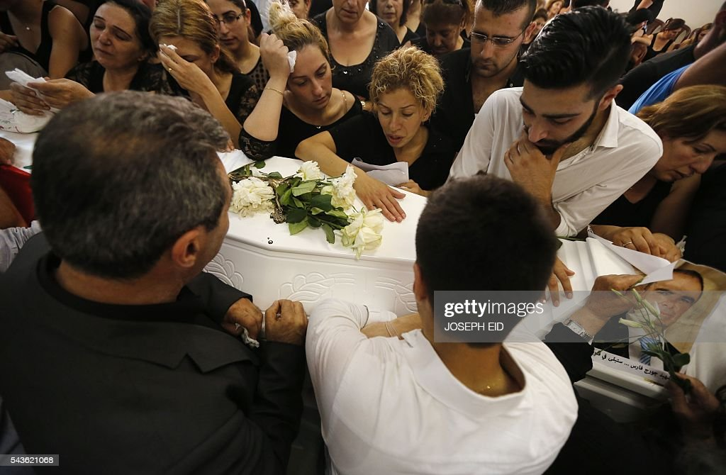 Lebanese Christians mourn over the coffins of relatives, who were killed in suicide attacks earlier this week, during their funeral in the village of al-Qaa, near the country's border with war-ravaged Syria, on June 29, 2016. Two waves of suicide bombings struck the predominantly Christian village on June 27, killing and wounding several people before dawn and in the evening. / AFP / JOSEPH EID