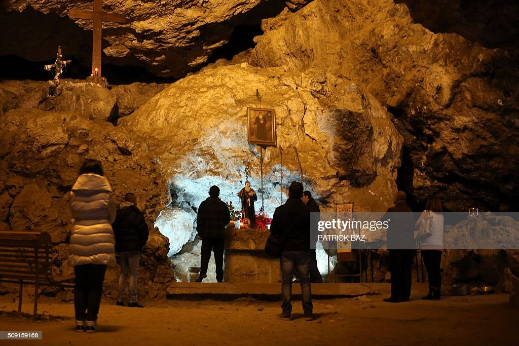 Lebanese Christians pray at the grotto of Saint Anthony the Great in Qozhaya in the Qannoubine valley in northern Lebanon on February 09, 2016. It is a local belief that St. Anthony visited his disciples in that cave dubbed the miraculous cave during his visit of the Holy Land. The miracles and the recoveries related to St. Anthony, that occurred in this cave confirm this hypothesis. Anthony was a Christian monk from Egypt, revered since his death as a saint. He is also known as the Father of All Monks. / AFP / PATRICK BAZ