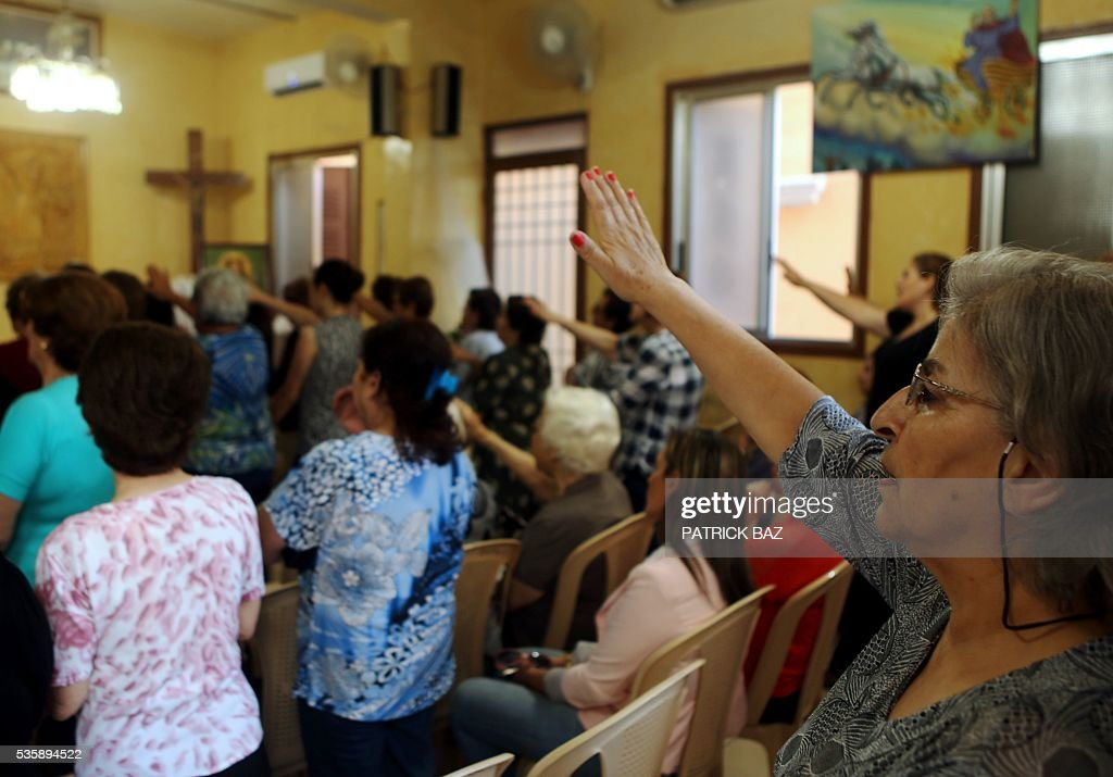 Lebanese Christians sing Ave Maria as they raise their hands to salute Virgin Mary prior to a procession marking the month of Virgin Mary in the Beirut Christian dominated neighbourhood of Ashrafiyeh on May 30, 2016. / AFP / PATRICK BAZ
