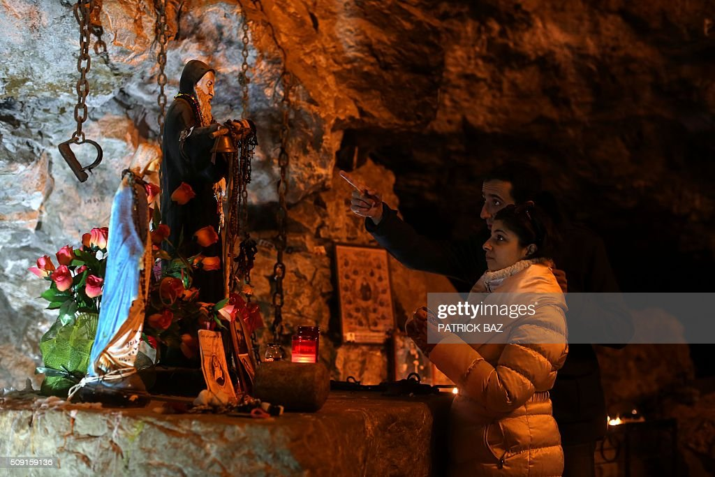 Lebanese Christians visit the grotto of Saint Anthony the Great in Qozhaya in the Qannoubine valley in northern Lebanon on February 09, 2016. It is a local belief that St. Anthony visited his disciples in that cave dubbed the miraculous cave during his visit of the Holy Land. The miracles and the recoveries related to St. Anthony, that occurred in this cave confirm this hypothesis. Anthony was a Christian monk from Egypt, revered since his death as a saint. He is also known as the Father of All Monks. / AFP / PATRICK BAZ