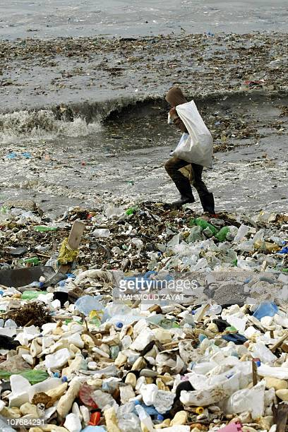 A Lebanese collects recyclable waste as he walks along a garbage dump spilling into the Mediterranean sea in the southern Lebanese city of Sidon as...