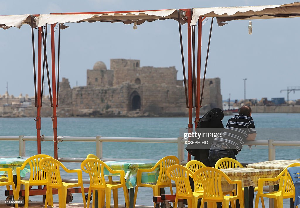 A Lebanese couple stands across the Sidon Sea Castle, a fortress built by the Crusaders, as clashes between the Lebanese army and supporters of a radical Sunni cleric continued in the southern city's Abra district on June 24, 2013. At least sixteen soldiers have been killed in clashes with supporters of Sheikh Ahmad al-Assir in southern Lebanon, the army said, in violence tied to rising sectarian tensions fanned by the Syria conflict.