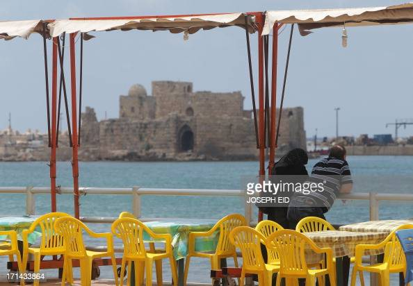 A Lebanese couple stands across the Sidon Sea Castle a fortress built by the Crusaders as clashes between the Lebanese army and supporters of a...