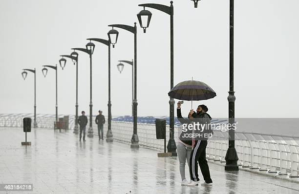 A Lebanese couple takes a selfie under the rain as they walk at Beirut's seaside corniche in Ain alMreisseh during a heavy storm on February 11 2015...