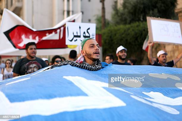 Lebanese demonstrators hold placards and banners as they head from the Ministry of Interior towards Beirut's Martyr's square during a mass rally...