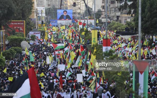 Lebanese demonstrators march with their national flags and the flags of Palestine and the militant Shiite movement Hezbollah during a protest against...